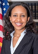 Headshot of Miss Bethel, dark haired smiling woman with blazer and collared shirt in front of American flag and bookcase.