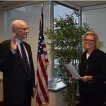 Tall man being sworn in by a woman in front of American flag