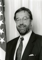 Bearded gentleman with eyeglasses smiling next to American flag