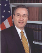 A gentleman wearing glasses a dark suit and dark yellow tie tie smiling for the camera in front of a row of books and an American flag.