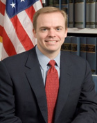 A gentleman with light brown hair, a dark blue suit and red tie smiling for the camera