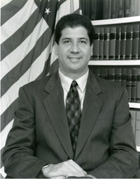 A seated gentleman wearing a dark suit smiling for the camera in front of a row of books and an American flag