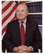A distinguished gentleman wearing a dark suit and red tie smiling at the camera in front of a row of books and an American flag.