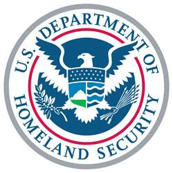 A circle with a blue and white drawing of an eagle with wings spread and grasping an olive branch and arrows in either talon. A crest on the eagles chest has a line drawing of stars, mountains and rivers. Words around the exterior read the US Department of Homeland Security