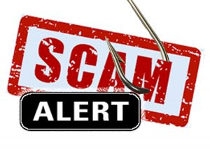 """A sign with the words """"scam alert"""" pierced by a fish hook"""
