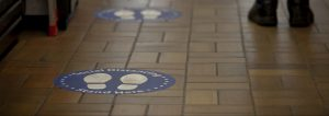 A brown tiled floor with blue circles with outlines of shoe soles indicating where a person should stand for appropriate social distancing
