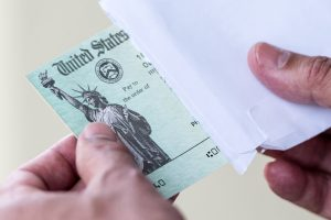 A green check issued by the US Treasury being pulled out of an envelope by an adult's hands