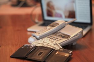 On a long brown table, an open wallet with 20 dollar bills and credit cards sits in front of a telephone and an open laptop computer. The laptop screen shows an out of focus image of an elderly person answering a phone.