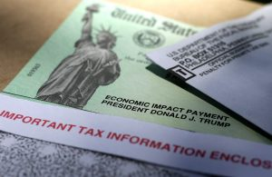 A green United States Treasury issued Economic Impact Payment check with an image of the Statue of Liberty and underneath an official Treasury Department envelope
