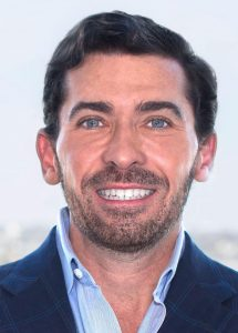 A person with a blue suit and open collar and close cropped dark beard smiling at the camera
