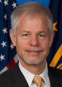 A person with greying hair and goatee wearing a dark suit and gold tie smiling at the camera in front of several flags.