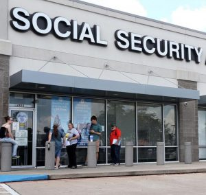 """A grey building with large glass windows and people lined up in front. The LArge letters on the front of the building read """"Social Security"""""""
