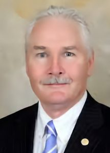 A person with gray hair and mustache wearing a black suit, gold lapel pin and purple striped tie smiling at the camera.