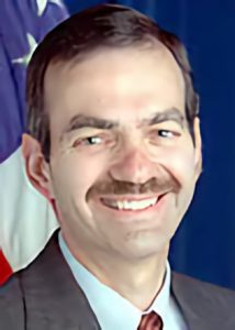A person with a dark mustache wearing a gray suit and red tie smiling at the camera in front of an American flag